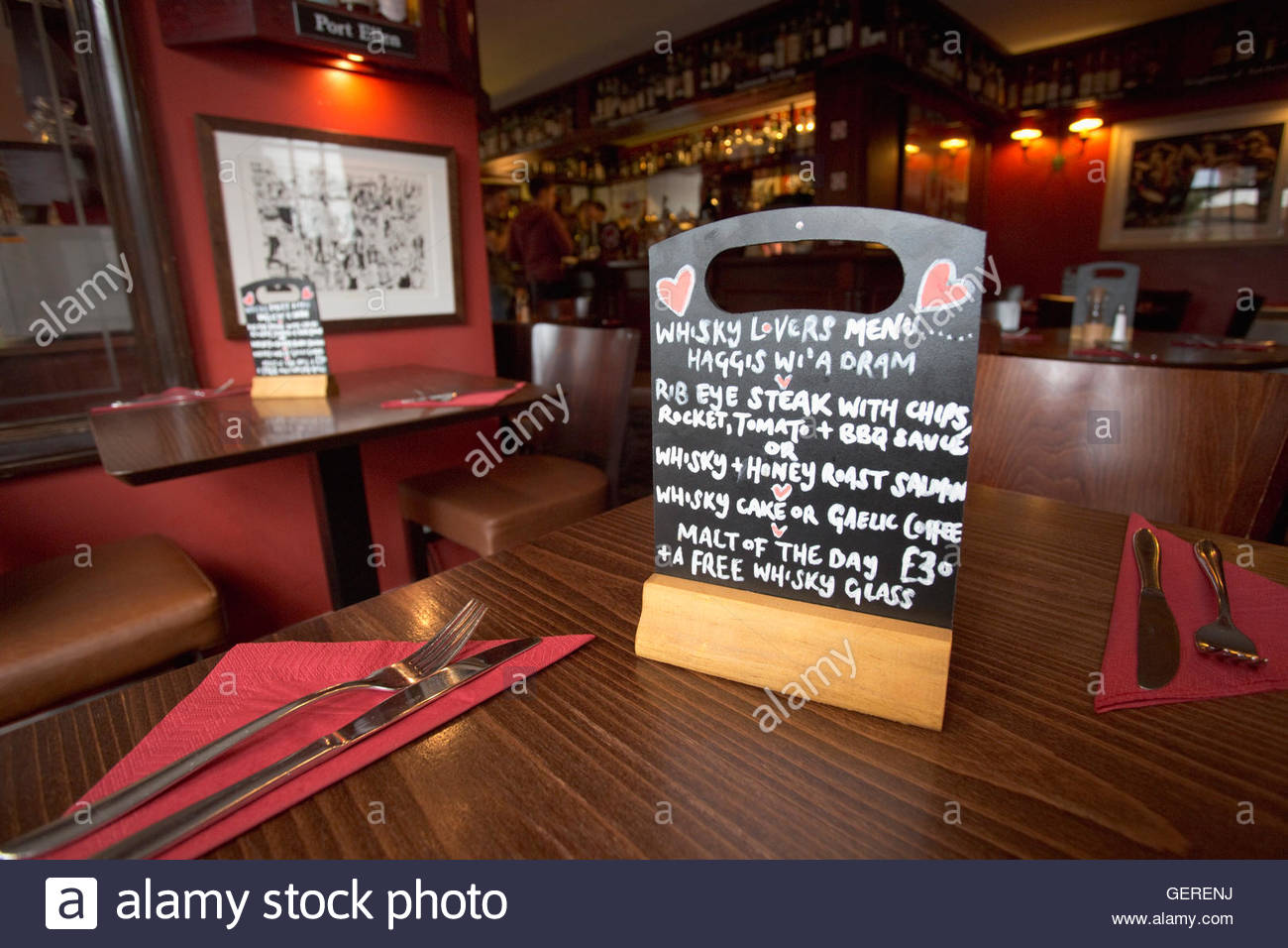 A small chalkboard menu on a table in the bar of the Fiddler's, Restaurant with Rooms, Drumnadrochit, Highlands - Stock Image