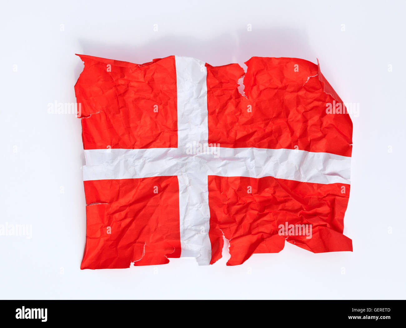 A crumpled and torn paper Dannebrog flag, the Danish flag. Close to being the happiest people? - Stock Image