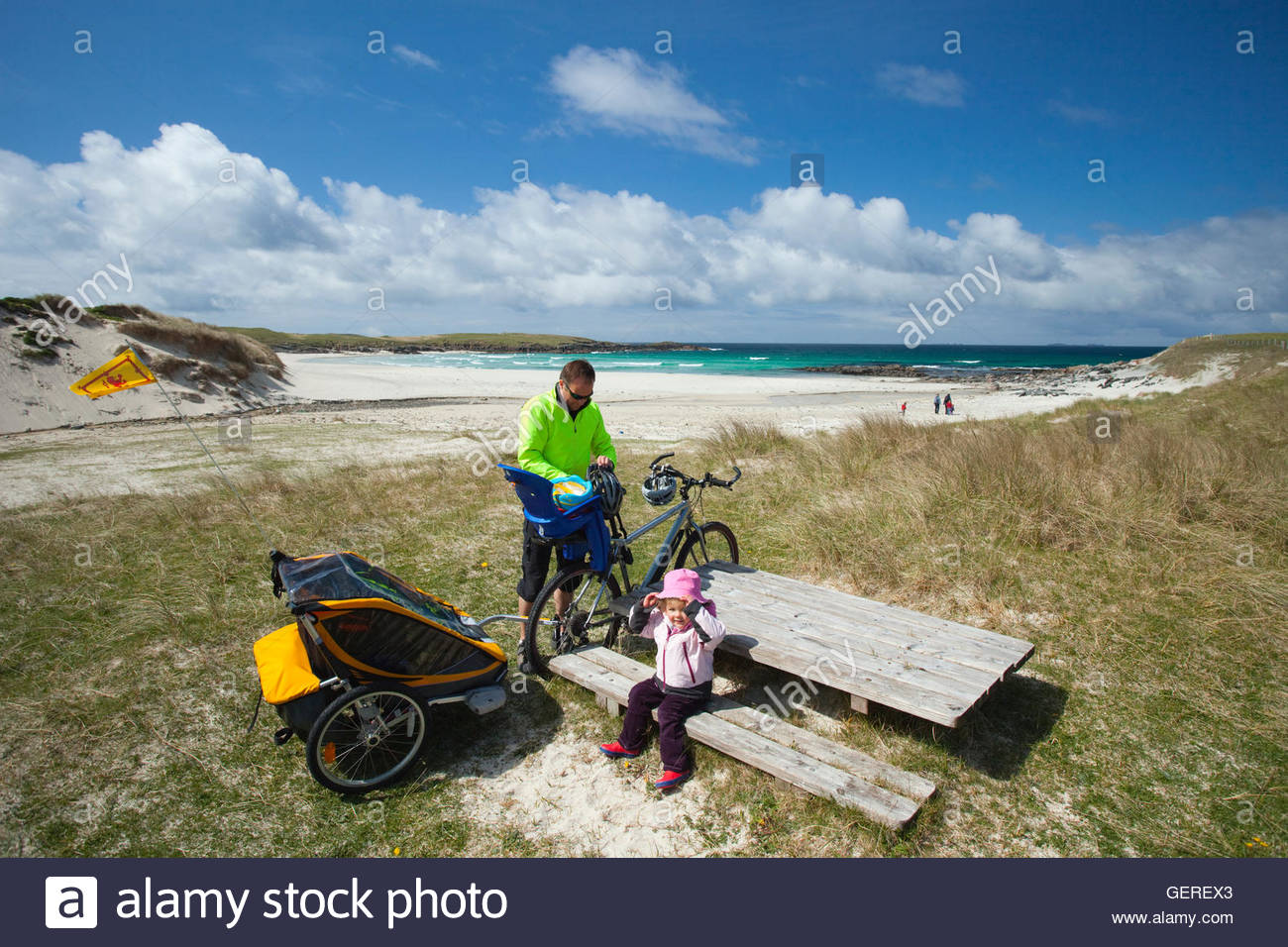 A family enjoy a day on Hosta Beach or Traigh Stir after cycling there, North Uist, Outer Hebrides, Scotland. - Stock Image