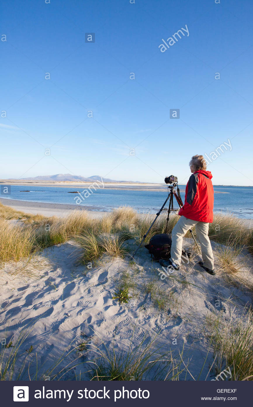 A wildlife photographer with a camera and tripod  in the dunes above the white sandy beach at, Isle of Benbecula, - Stock Image