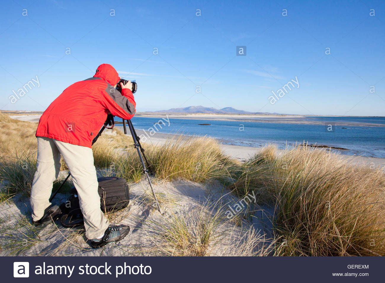 A wildlife photographer with a camera and tripod  in the dunes above the white sandy beach at, Isle of Benbecula, Stock Photo