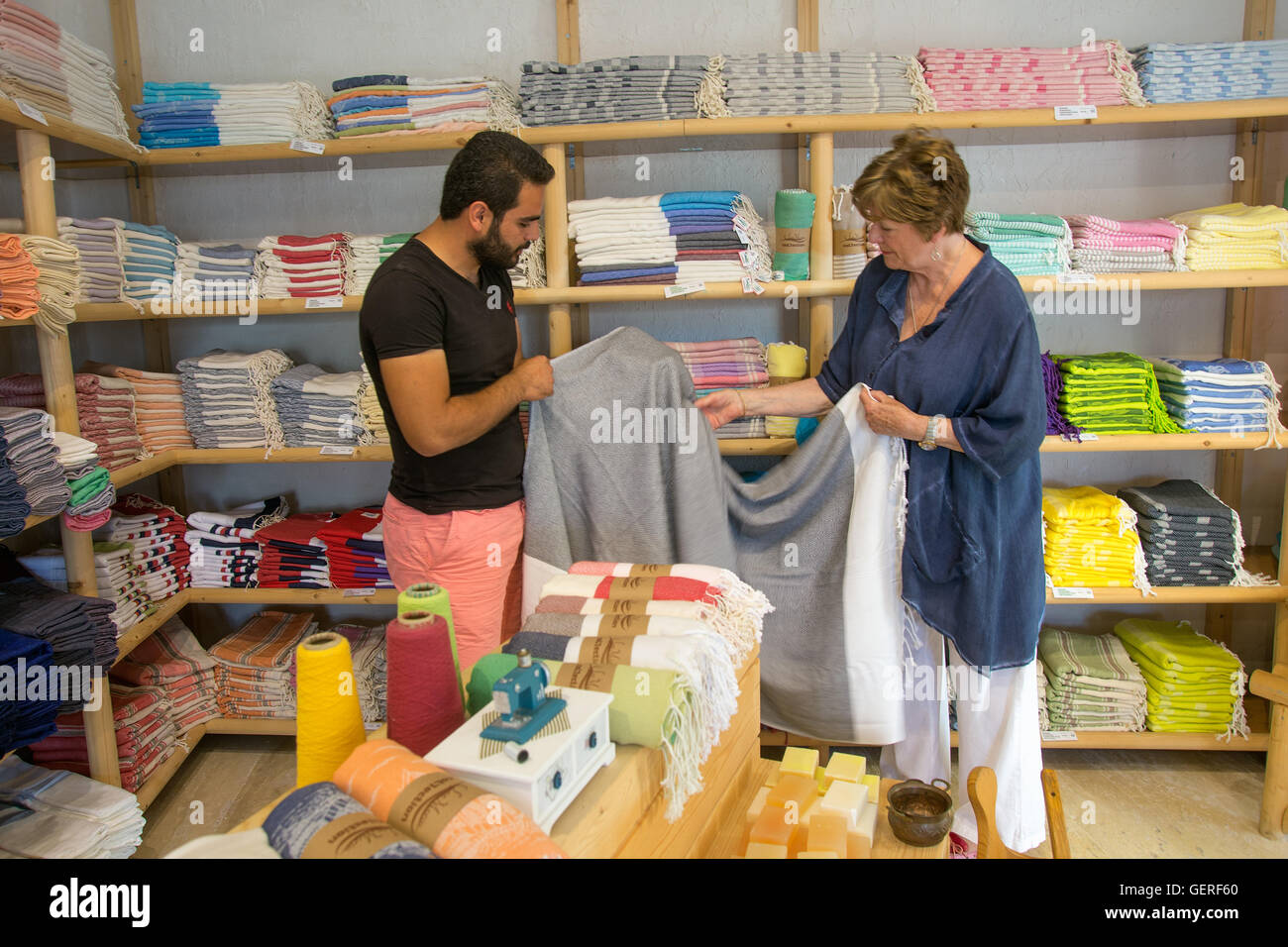 Owner and client in towel shop with display in Kalkan Turkey, - Stock Image