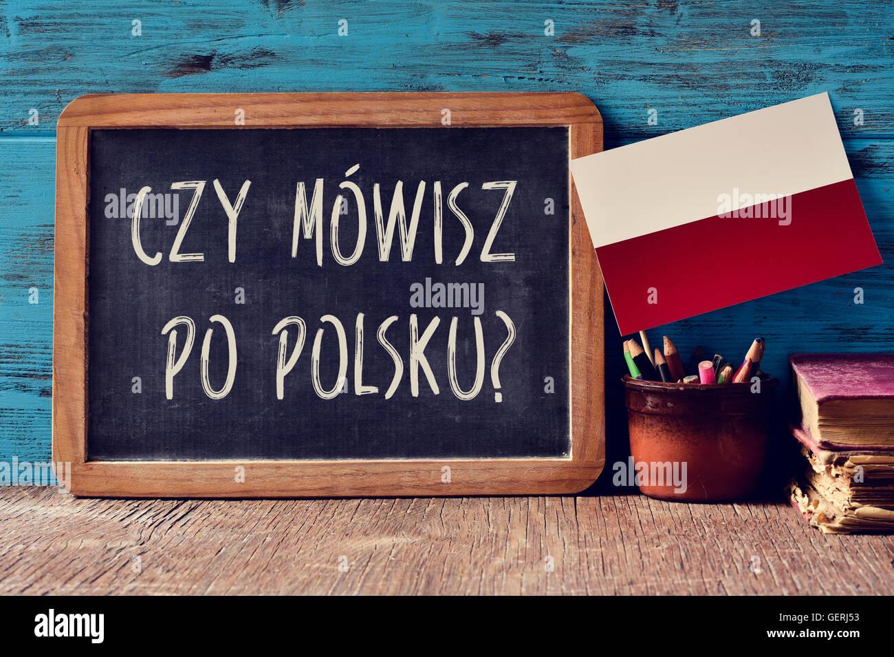 a chalkboard with the question czy mowisz po polsku?, do you speak Polish? written in Polish, a pot with pencils, - Stock Image