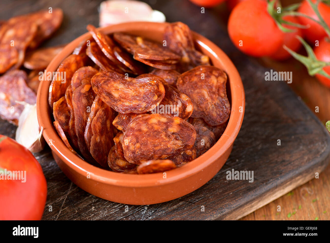 closeup of an earthenware bowl with some slices of Spanish chorizo, a pork sausage typical of Spain, on a rustic Stock Photo