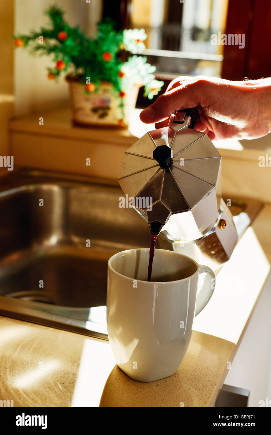 closeup of a young caucasian man serving coffee in a white mug from a moka pot in the kitchen - Stock Image