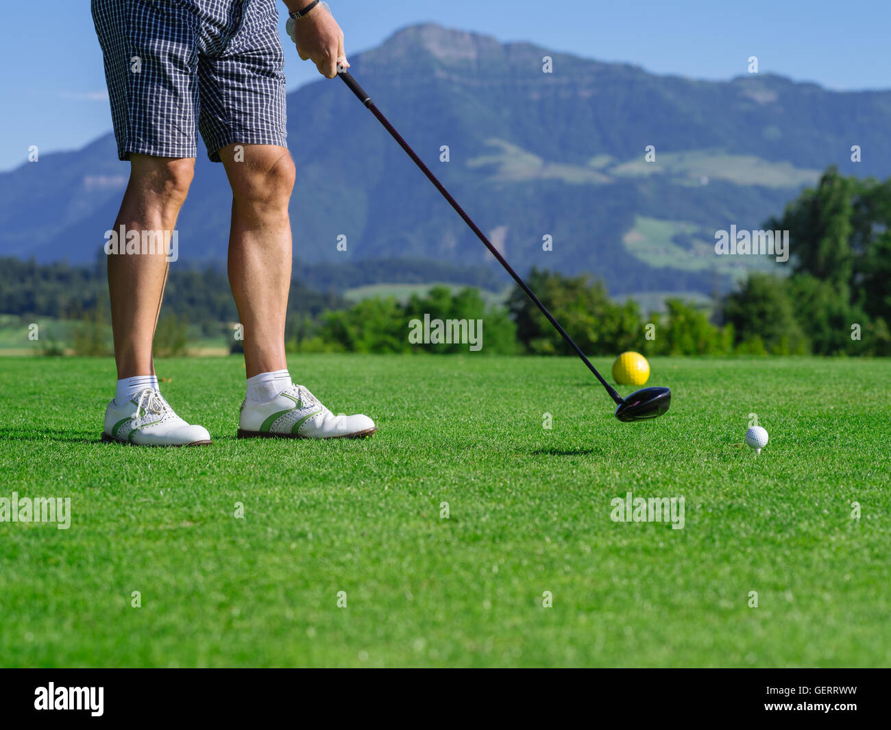Photo of a male golfer teeing off on a golf course on a beautiful day. - Stock Image