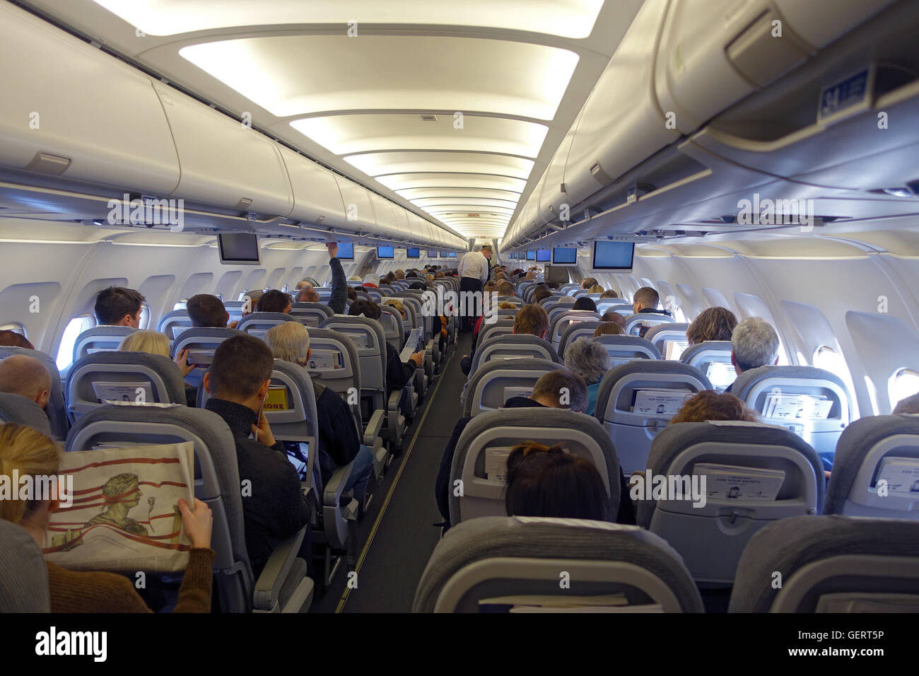 Vantaa, Finland, passengers and cabin crew in an aircraft cabin - Stock Image