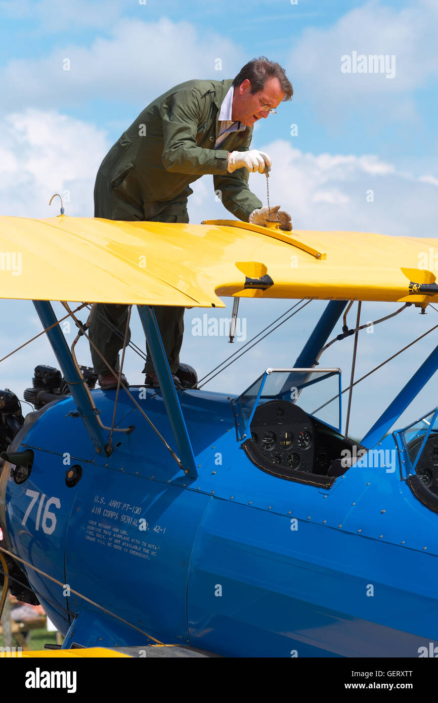 Pilot checks his wing fuel tanks on a Boeing Stearman PT-13 Kaydet vintage biplane built in 1943 as a trainer for - Stock Image