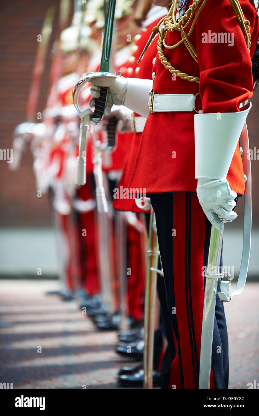 Close up of a British Army soldier standing to attention during a parade with drawn sword. - Stock Image