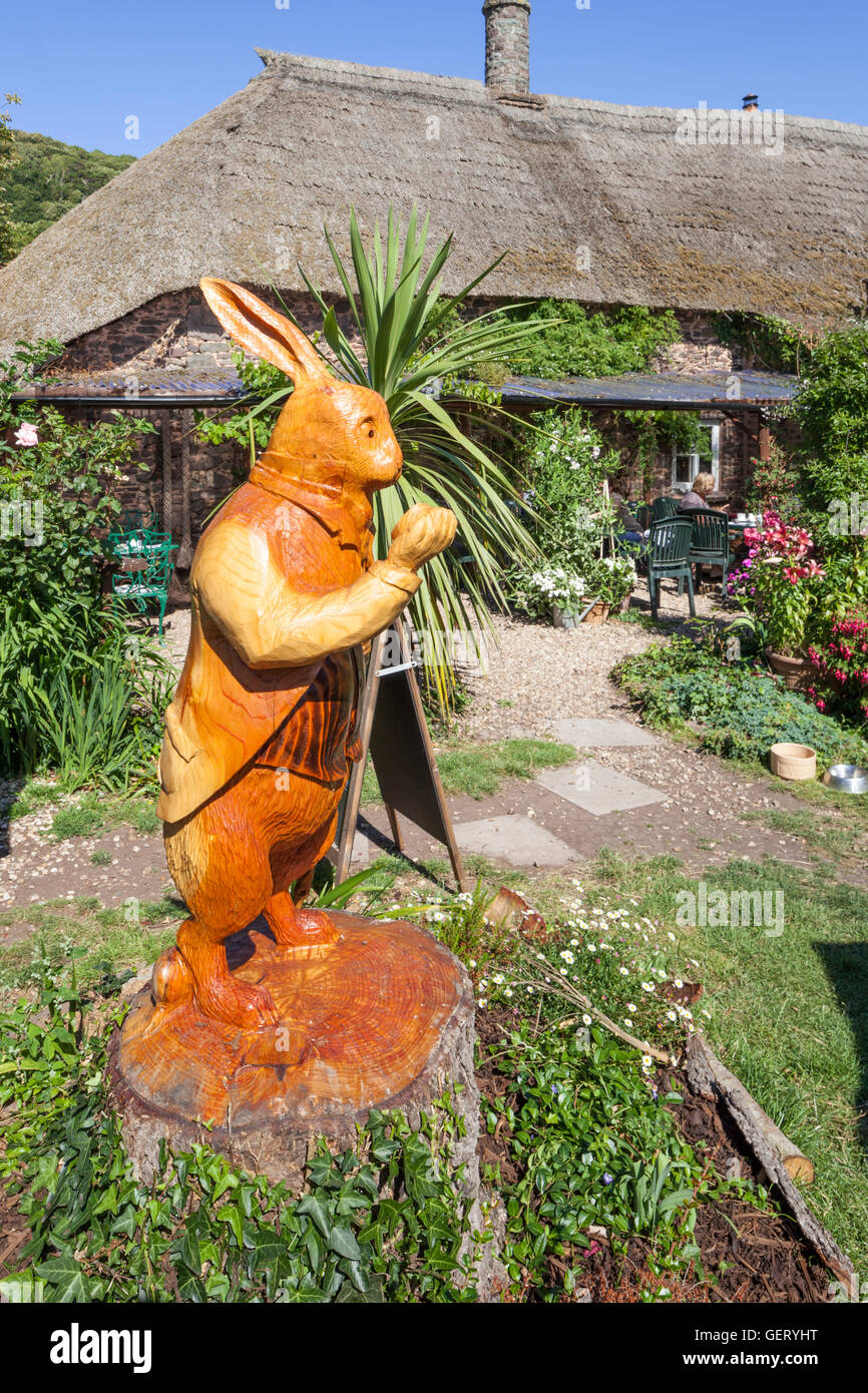 The White Rabbit carved from a tree trunk in the garden of Kitnors Tea Room in the Exmoor village of Bossington, - Stock Image