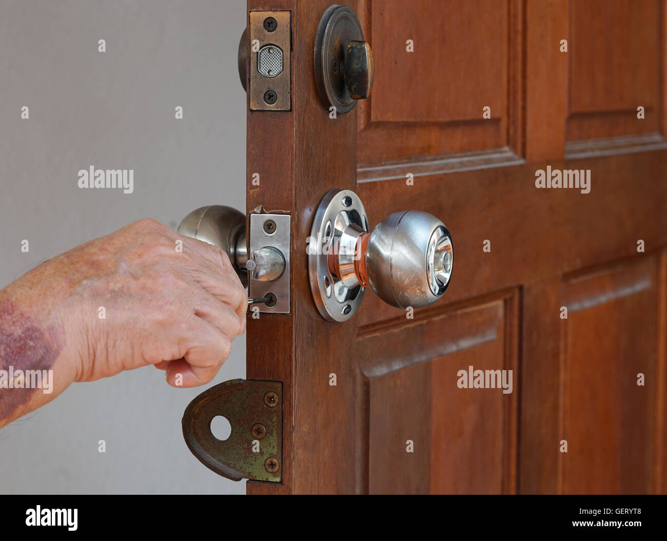 old locksmith maintain lock on vintage old door - Stock Image