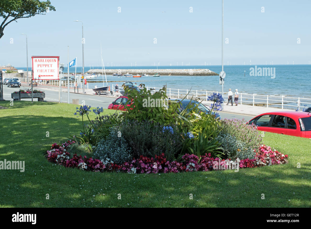 Flower bed looking towards breakwater and harbor at Rhos on Sea North Wales Stock Photo