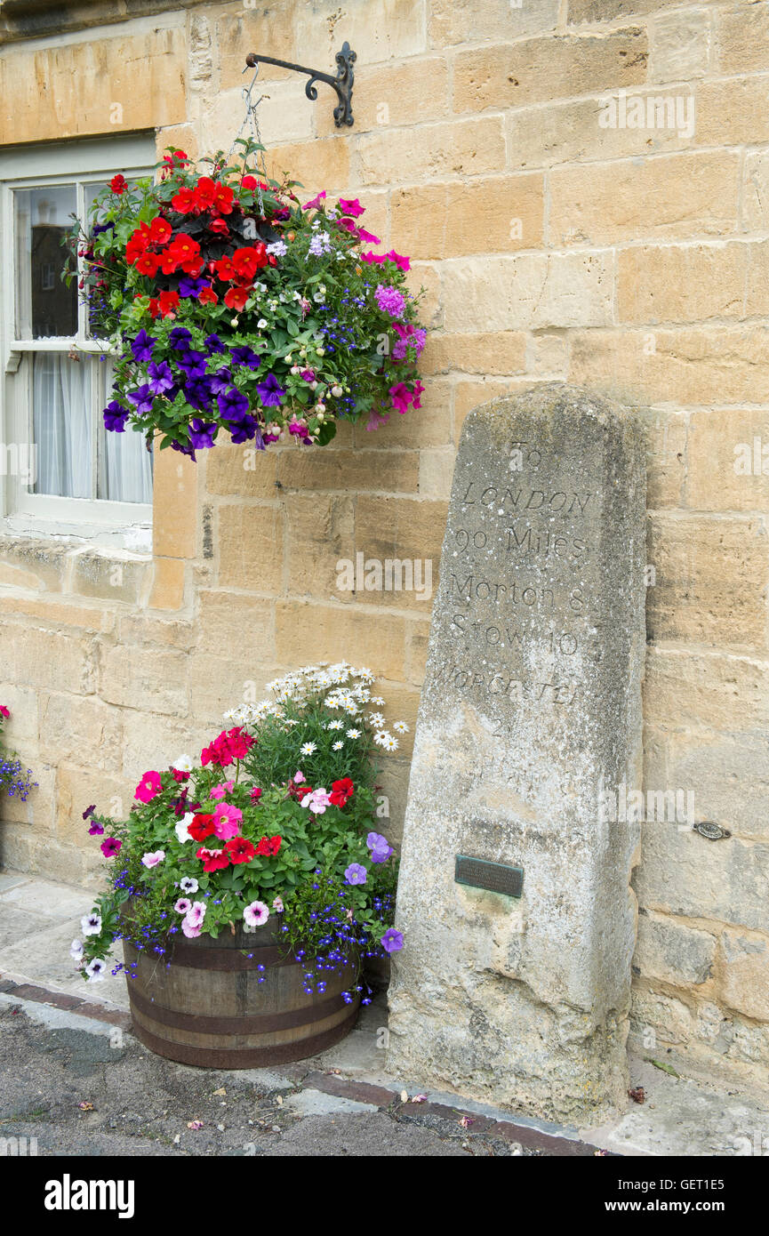 Old milestone, hanging basket and flower tub at the front of Stock ...
