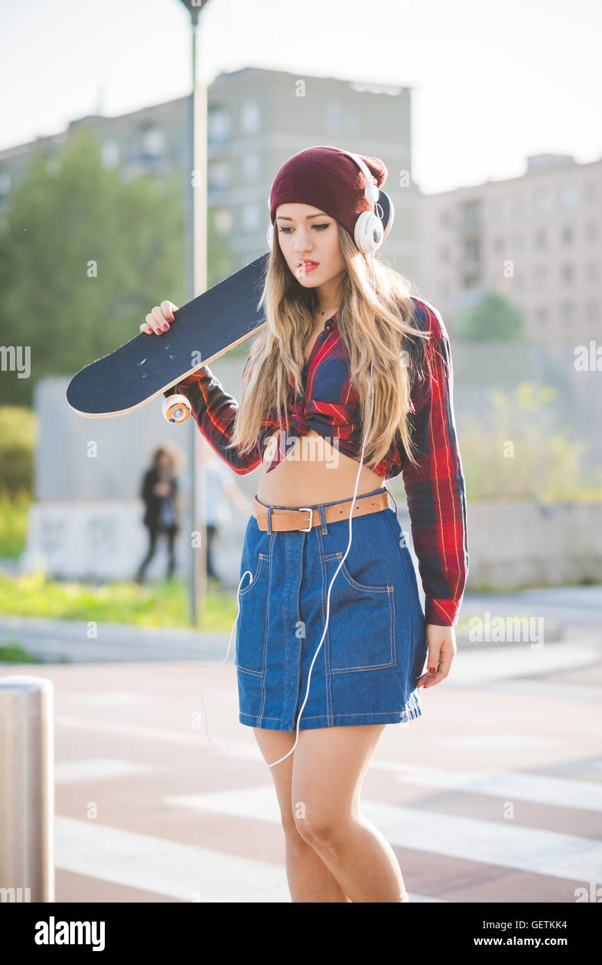 Half length of young beautiful blonde caucasian woman skater holding skateboard, listening music with headphones - Stock Image