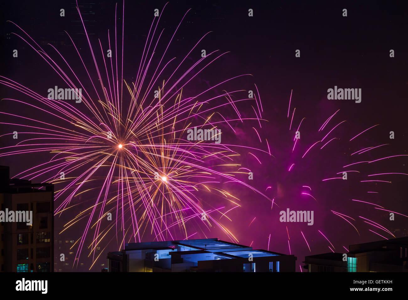 Multiple magenta pink fireworks burst above buildings - Stock Image