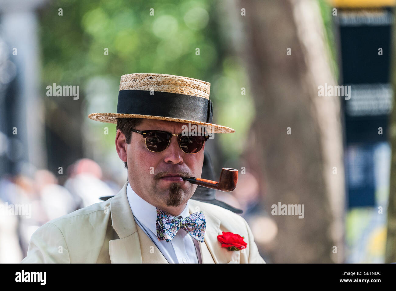 A chap wears a traditional straw boater and smokes a pipe at the Chap Olympiad. - Stock Image