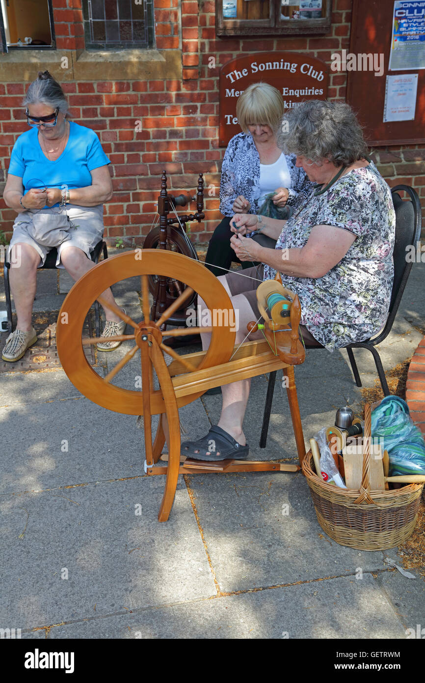 Two ladies sitting by their spinning wheels 'teasing' out the wool ready to go onto the spinning wheel to - Stock Image