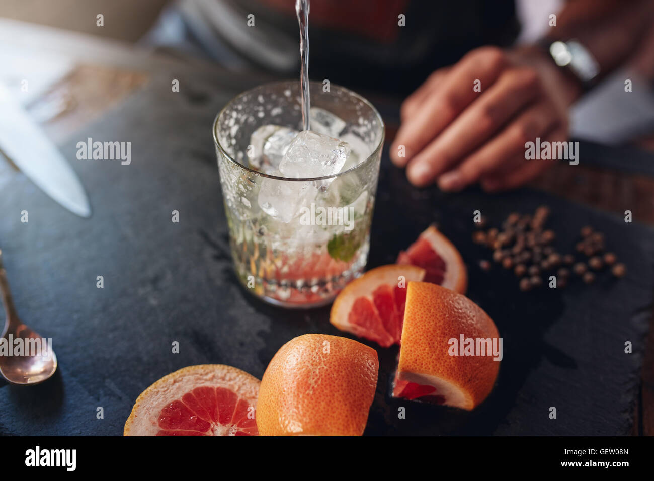 Closeup shot of bartender pouring drink into a glass full of ice cubes with cut grapefruits and peppercorn on counter. - Stock Image