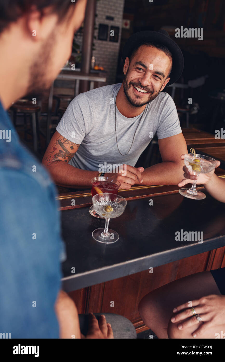Happy young caucasian man sitting at a coffee shop with his friends. Young friends sitting at a cafe table having - Stock Image