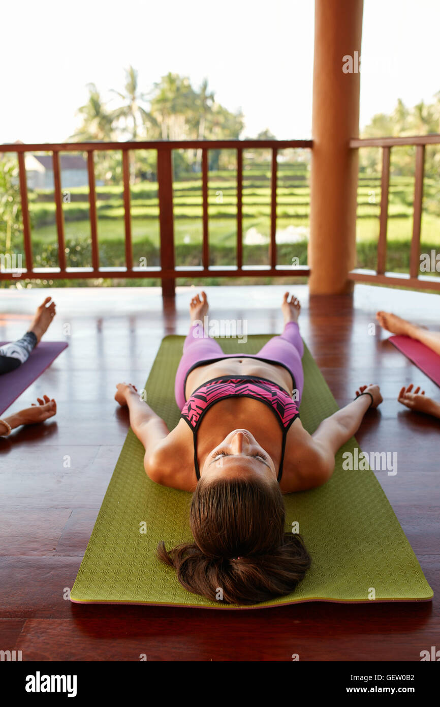 Image of fit young woman relaxing on yoga mat. Female lying on floor, savasana pose at yoga class. Stock Photo