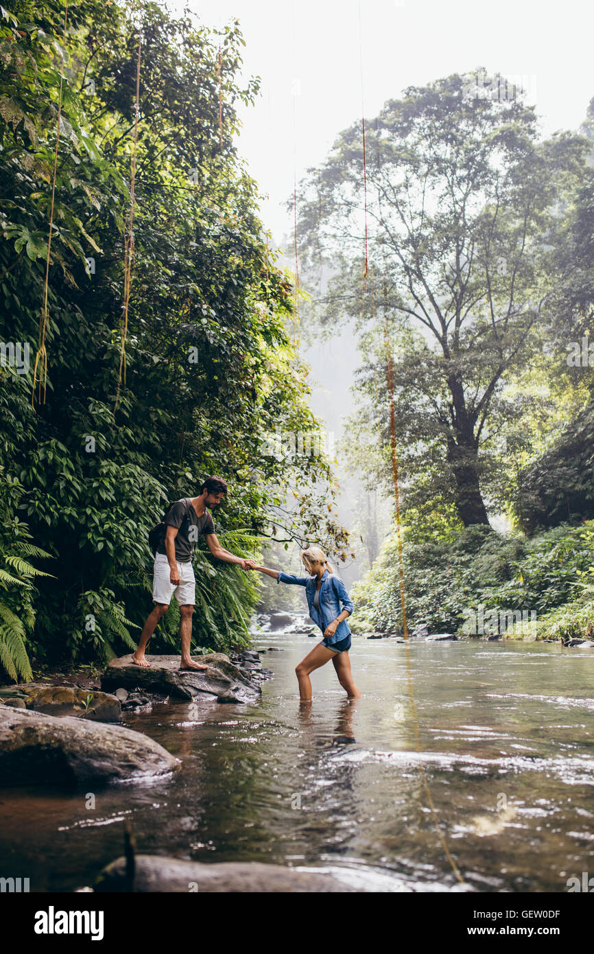 Outdoor shot of young man helping woman crossing stream. Couple in forest crossing the creek. Stock Photo