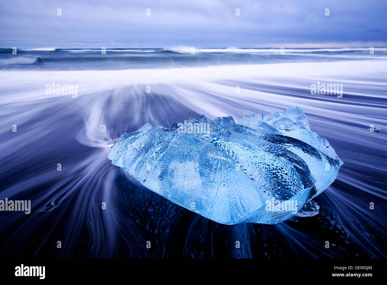 Waves washing around a small iceberg on the beach at Jokulsarlon in Iceland. Stock Photo