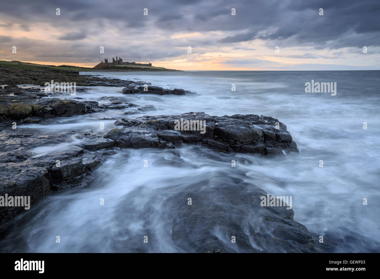 Dunstanburgh Castle viewed from the south with a stormy sea in the foreground. - Stock Image