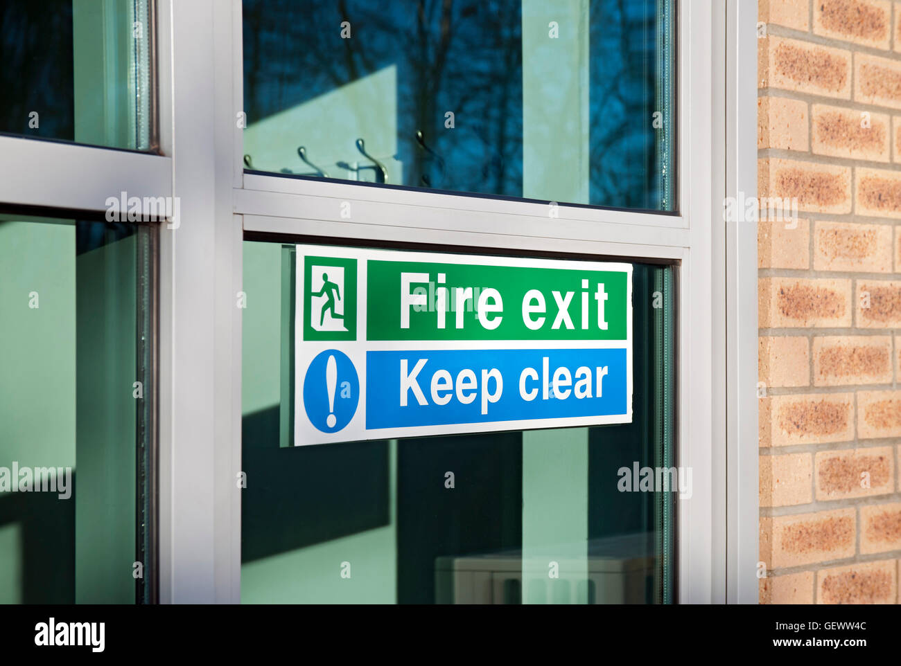 Fire exit and keep clear signs on glass door. Stock Photo