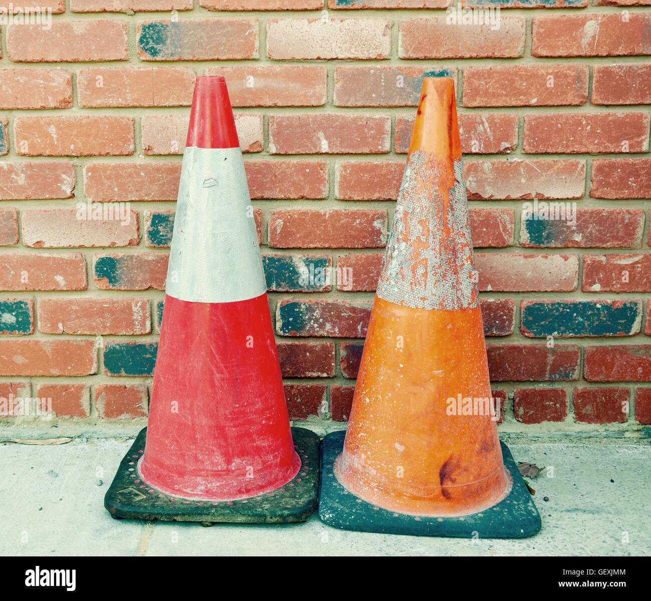 Two construction safety cones, red and orange with reflectors, isolated on a concrete sidewalk with brick background. - Stock Image
