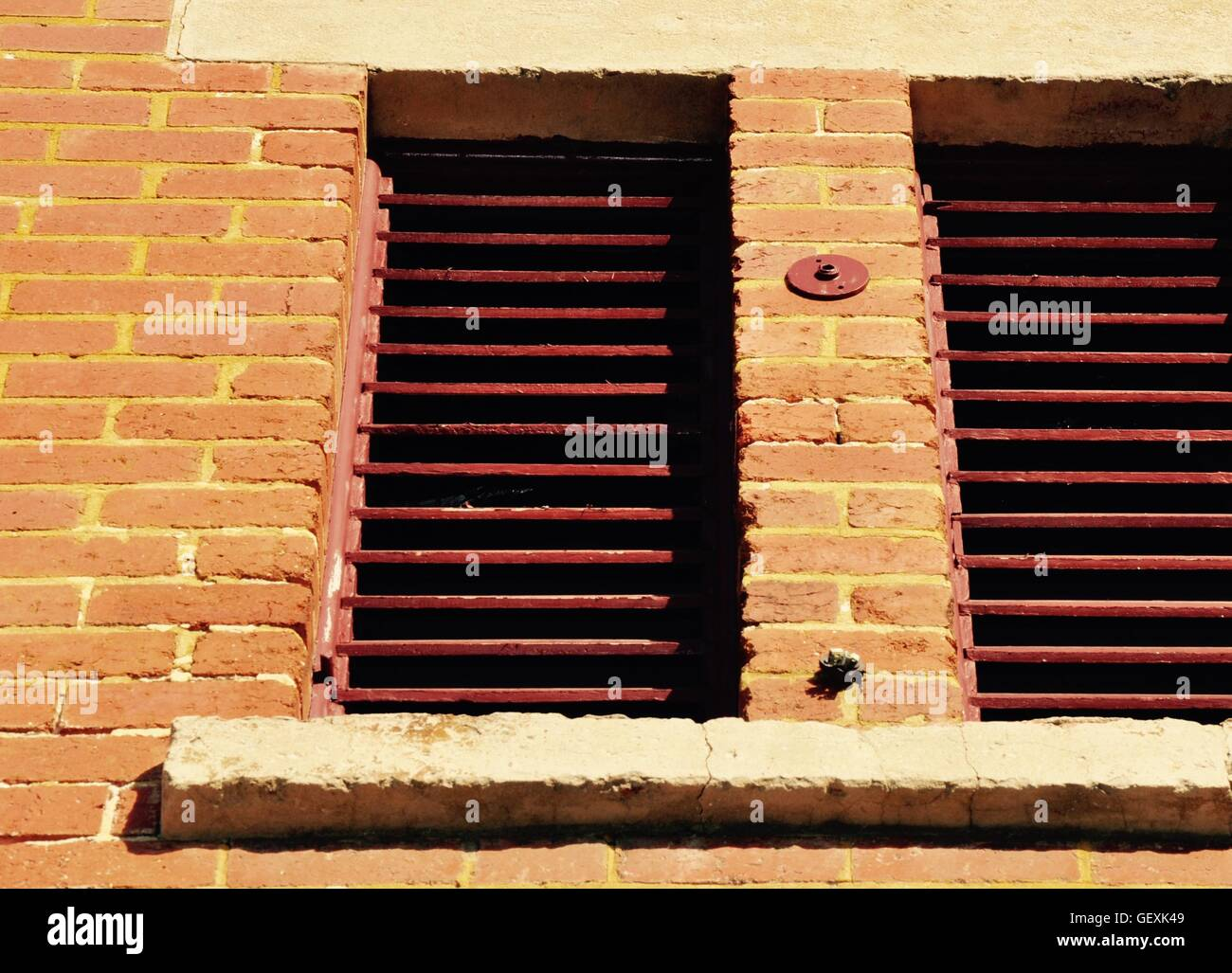 Wooden, brick red exterior plantation shutters with limestone ...