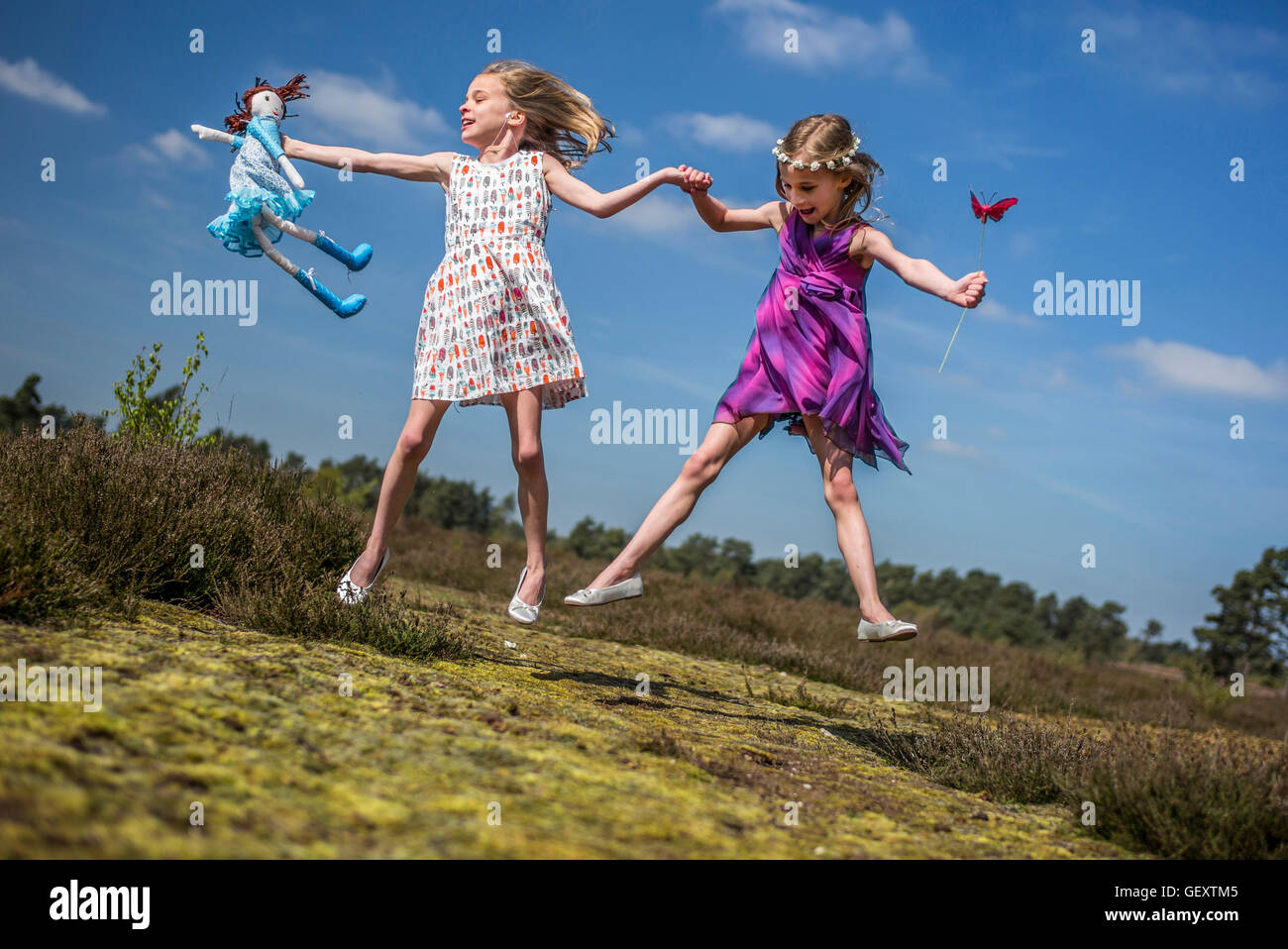 Identical twin sisters play together in the open air. - Stock Image