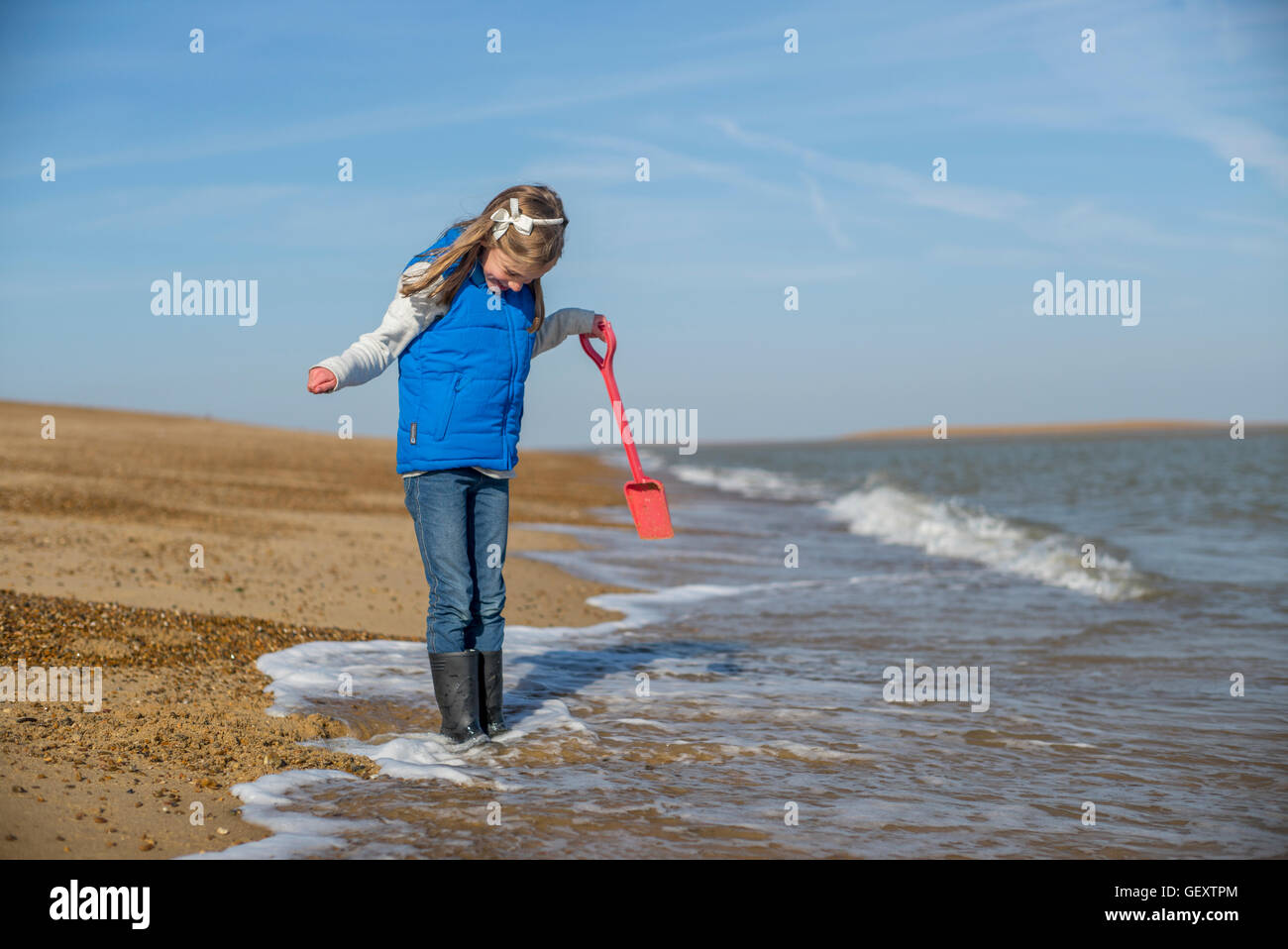 A young girl playing on the beach at Felixstowe. - Stock Image