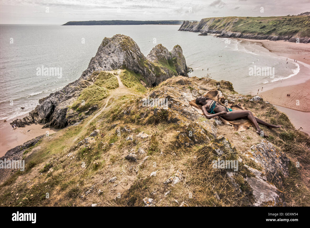 An afro caribbean woman relaxing on hills overlooking Three Clffs Bay on the Gower. - Stock Image