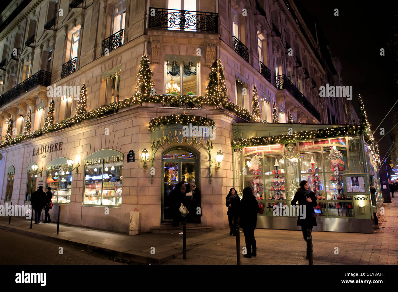 Bright lights and ostentatious shops of the Champs Elysees in Paris, France - Stock Image
