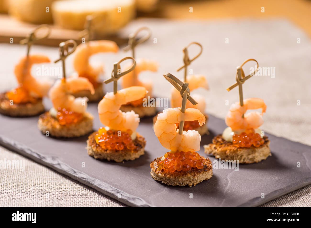 Shrimp Appetizer served on toasted bread with golden Caviar - Stock Image