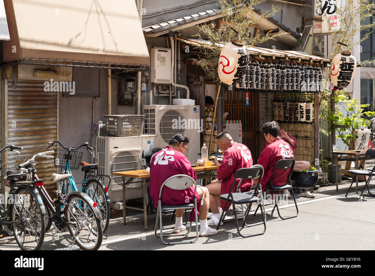 Three men take a break at a small restaurant during the sanja matsuri before continuing with the parade. Asakusa, - Stock Image