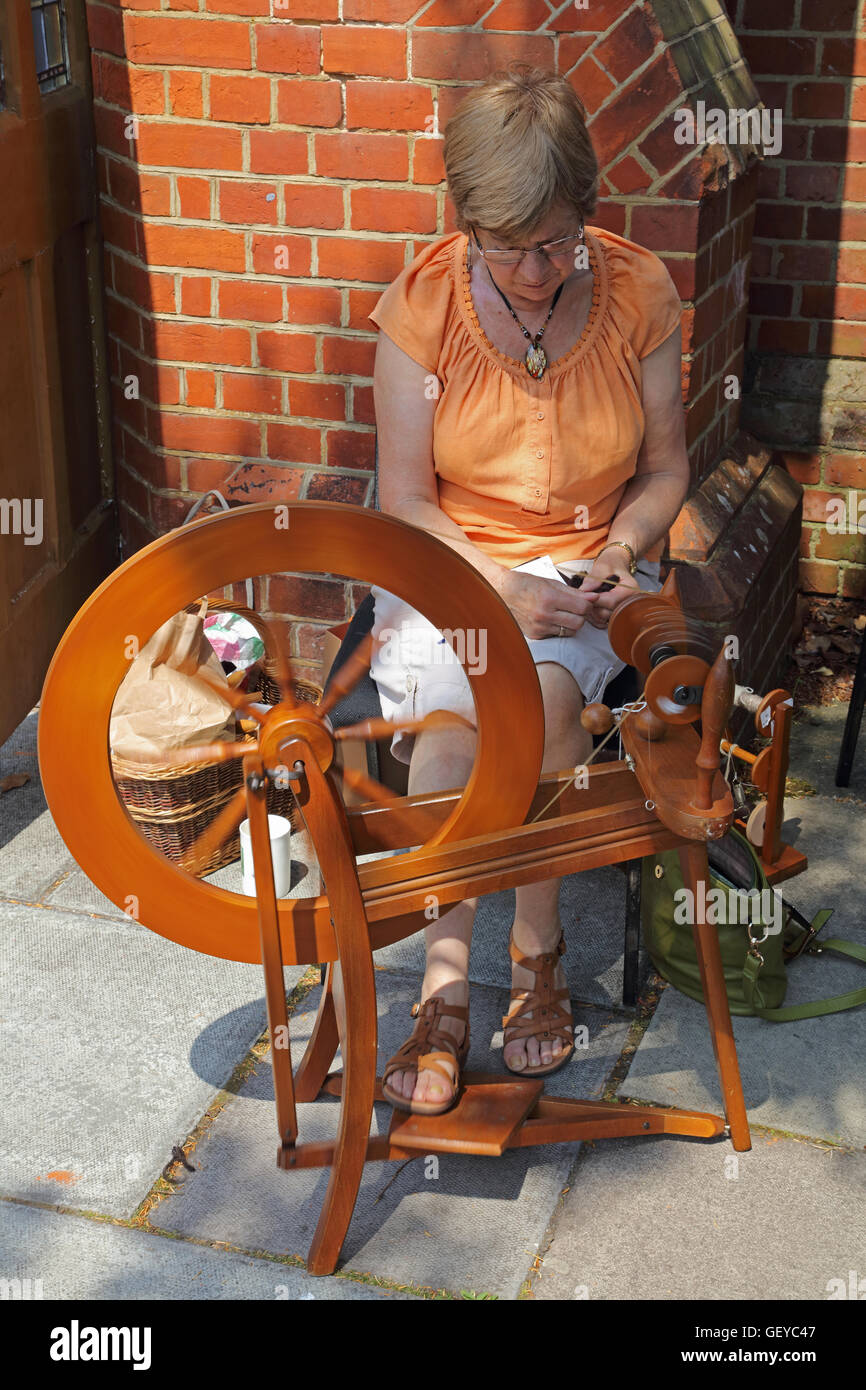 A lady sitting by her spinning wheel 'teasing' out the wool ready to go onto the spinning wheel to make - Stock Image