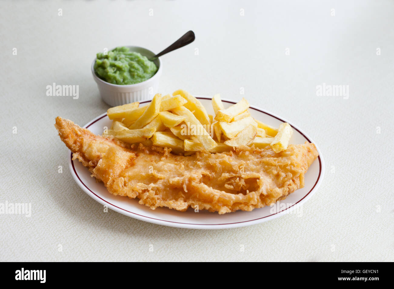 Traditional english meal - deep fried fish, cod with chips and mashed green peas, served in local restaurant in - Stock Image