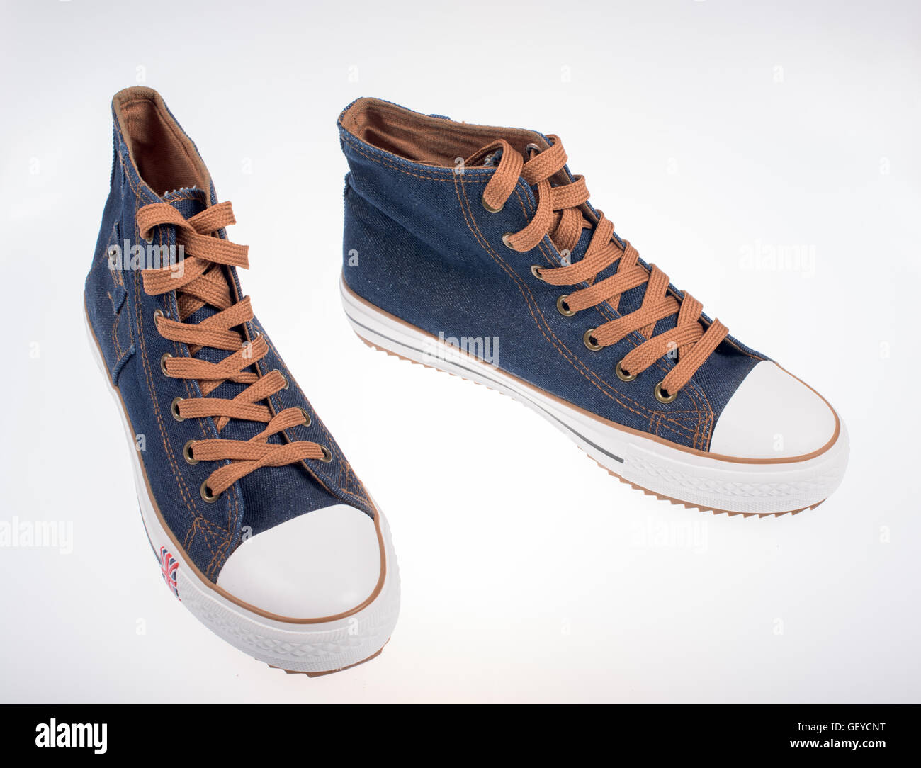 Sneakers made of denim on a white background - Stock Image