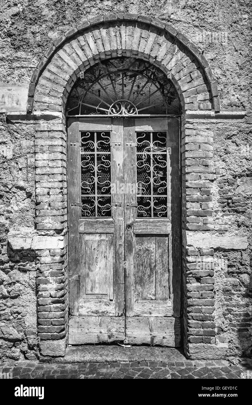 Old wooden door with upper railing and brick archway. - Stock Image