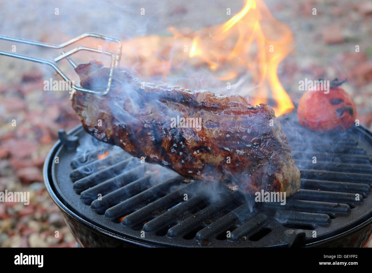 Steak on a barbeque held by tongs - Stock Image