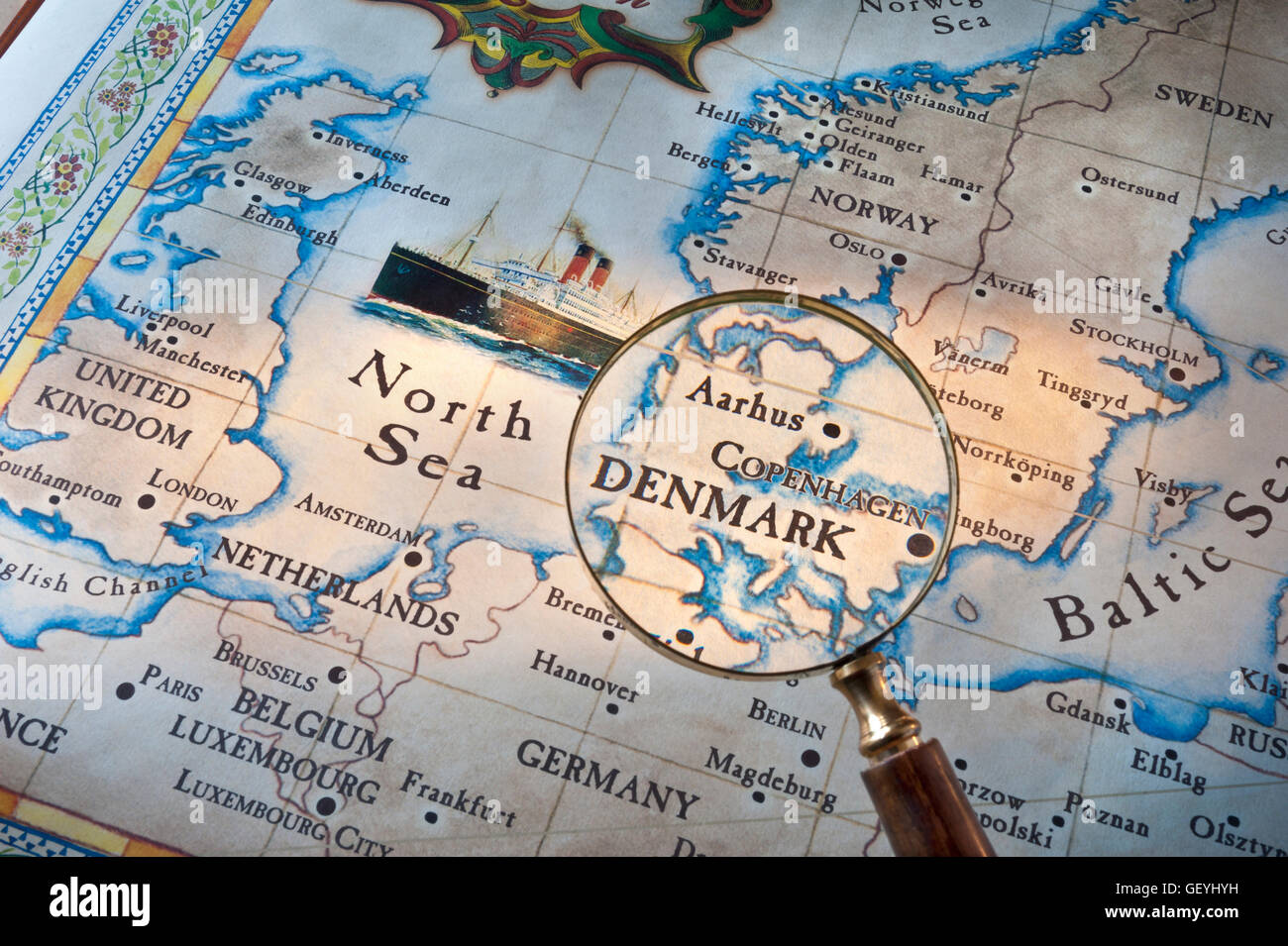Old style map with magnifying glass over Denmark-Copenhagen-Aarhus. Cruise ship featured in North Sea with UK & - Stock Image