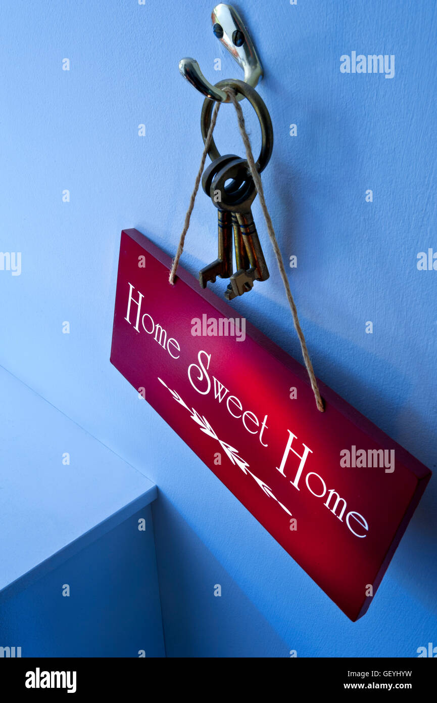 Moody atmospheric 'Home Sweet Home' sign hanging with home door keys on hook with small shaft of sunlight - Stock Image