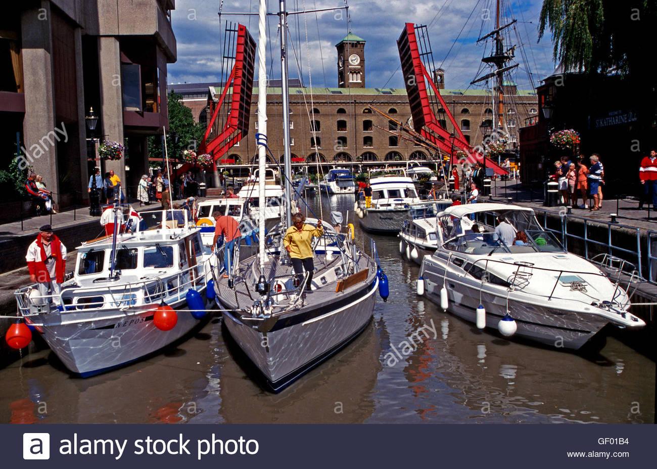 London, England, yachts at entrance of Saint Katharine's docks. folding bridge in background. - Stock Image
