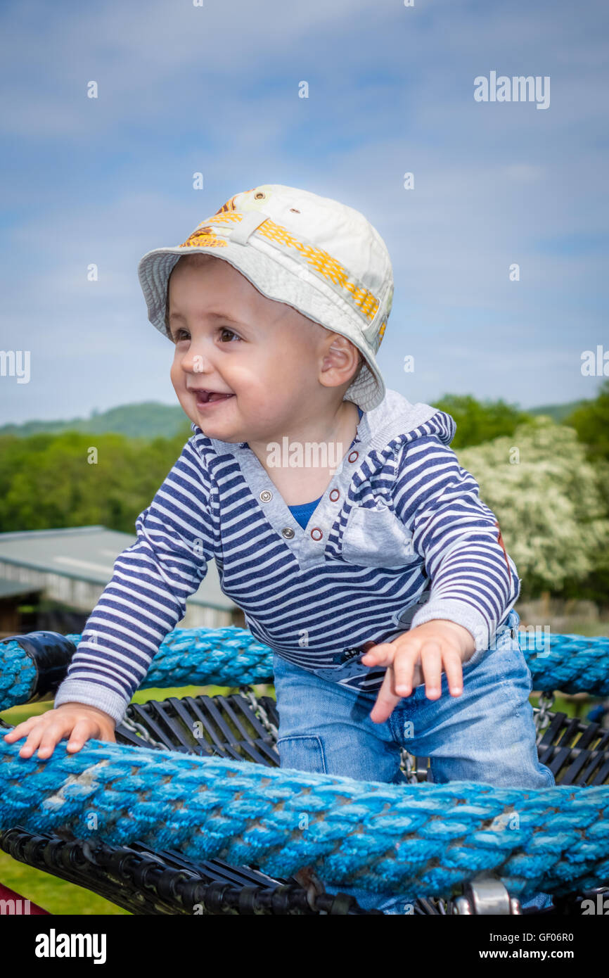 76cbeaf97 Cute little baby boy standing on a small carousel in the park playground