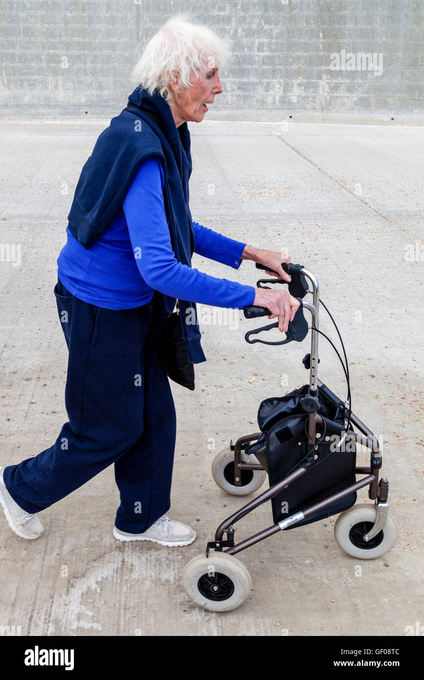 An Elderly Woman Walking With A Rollator Walking Aid, Rottingdean, Sussex, UK - Stock Image