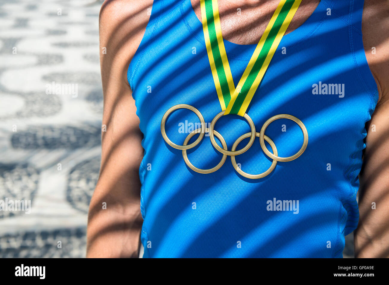 RIO DE JANEIRO - FEBRUARY 23, 2015: Athlete wearing Olympic rings gold medal standing under palm frond shadows. - Stock Image