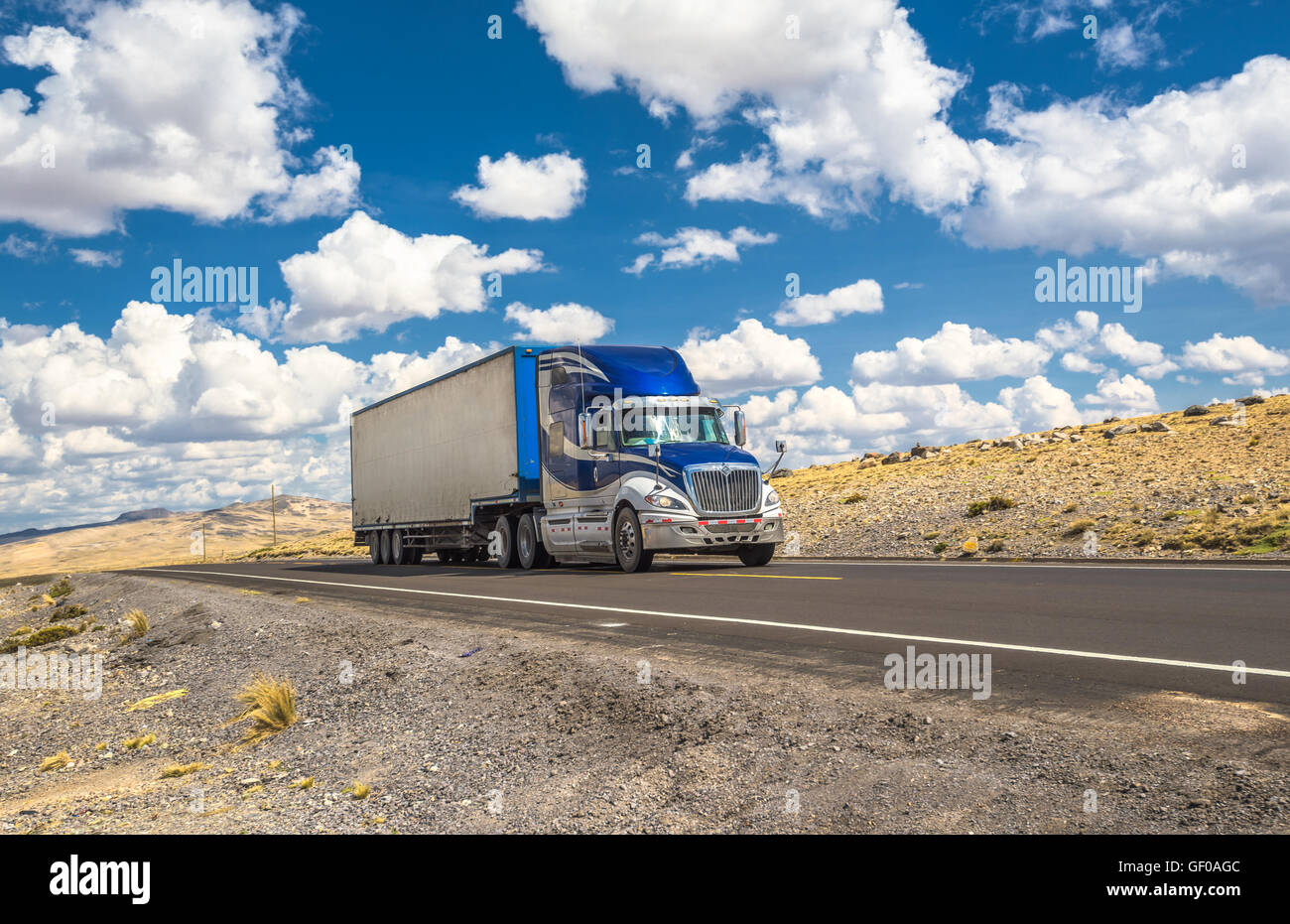 Blue truck moving on a highway - Stock Image