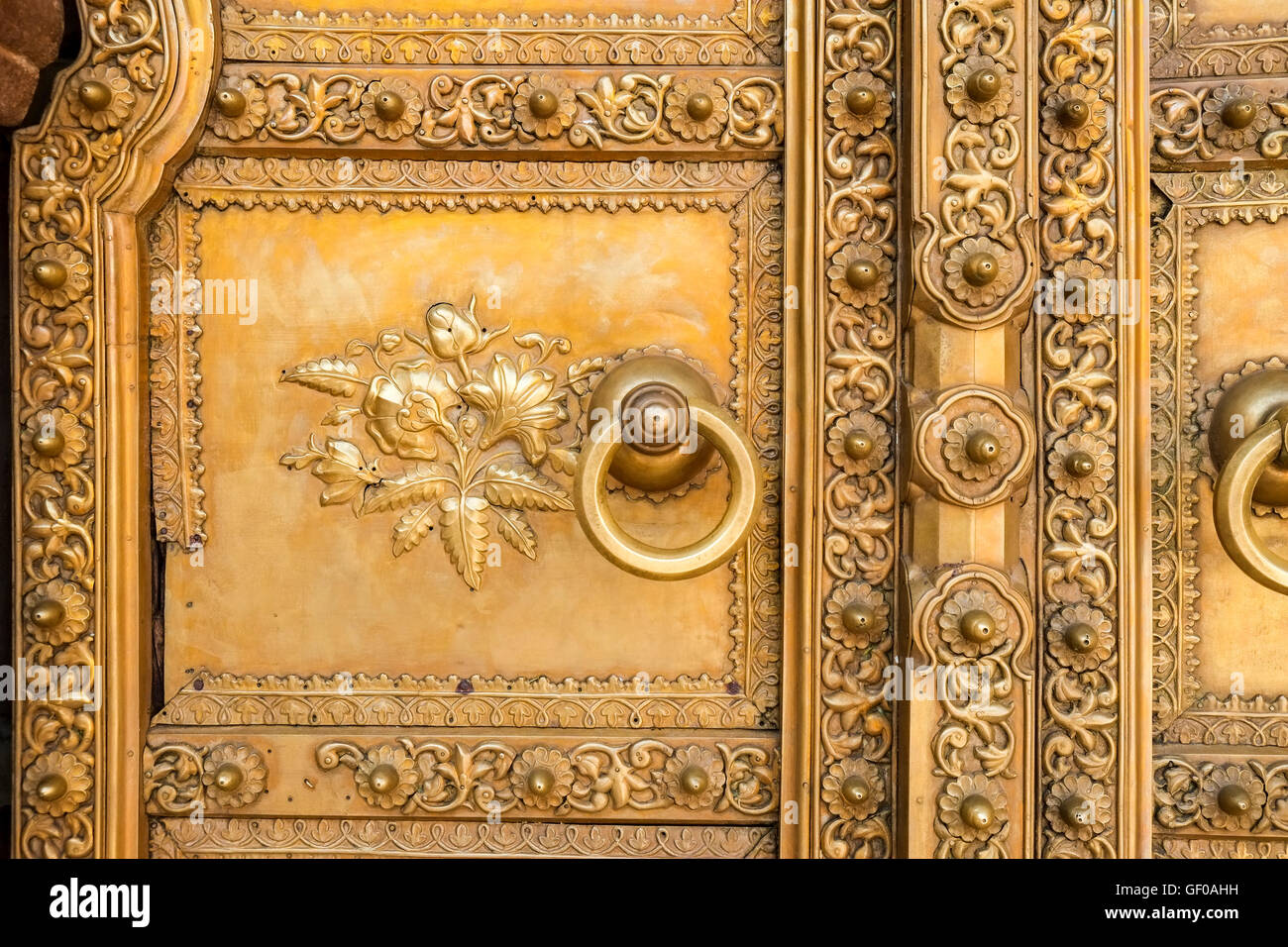 A gold-plated door and door handle at Chandra Mahal, one of the palaces in Jaipur's City Palace, Rajasthan, - Stock Image