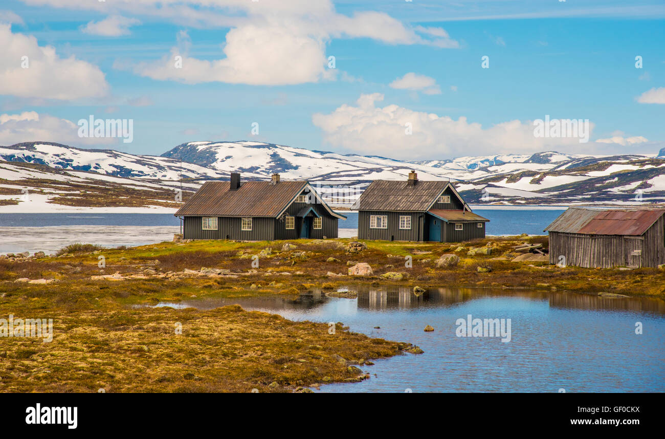 Lake Orteren in springtime rental cabins reflections. Hardangervidda National Park, Norway, Hordaland, Scandinavia, - Stock Image